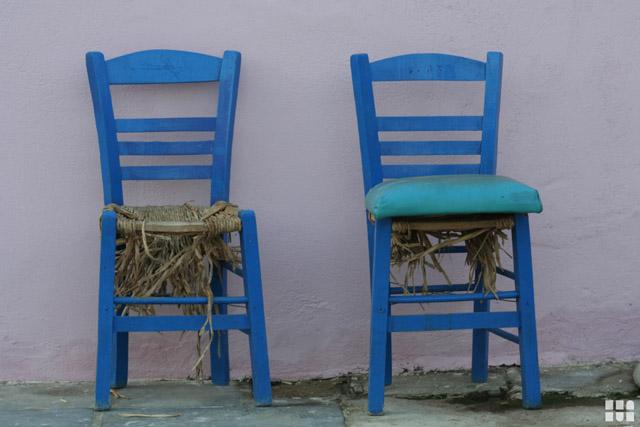 Blaue Stuehle an einer Hauswandmietwagen auf kreta