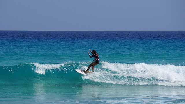 Frau auf Surfbrett Mietwagen Fuerteventura